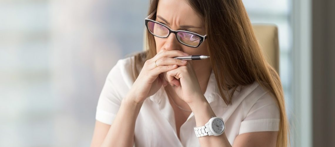 Worried businesswoman sitting alone in office. Pensive middle-aged woman resting her head on hands and looks aside in window. Concentrated female entrepreneur frowning thinking about problem solution