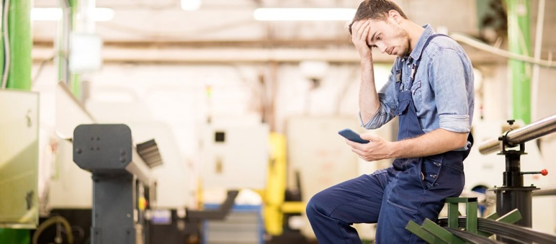 Embarrassed young engineer of factory reading notification in smartphone and touching his forehead