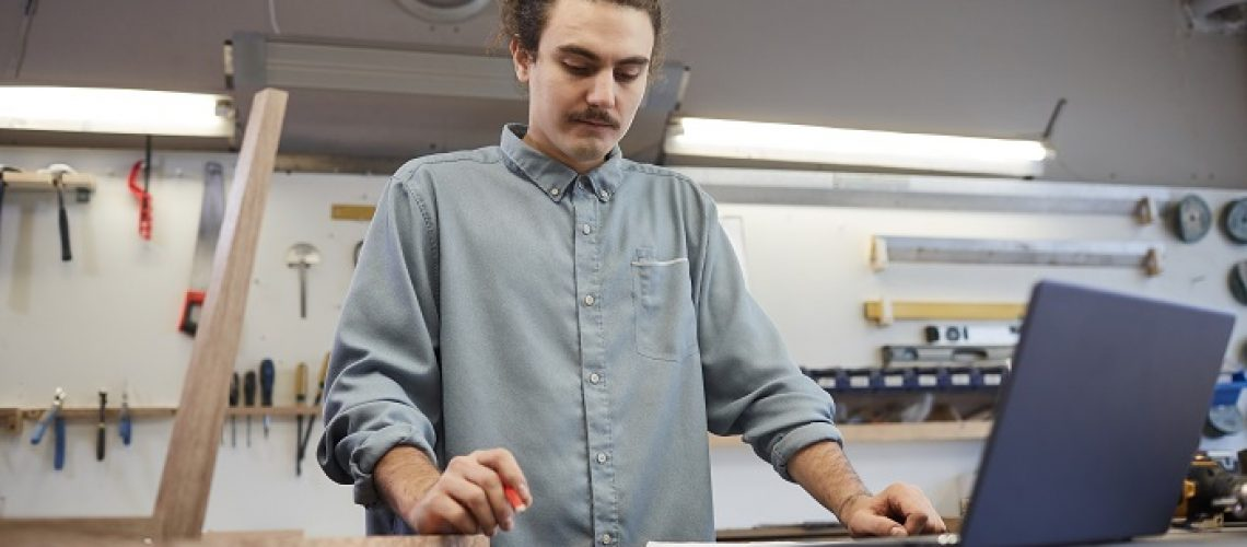 Young businessman standing at the table with laptop and examining document while working in workshop