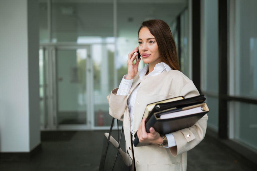 imagem-mulher-falando-ao-telefone-segundando-documentos