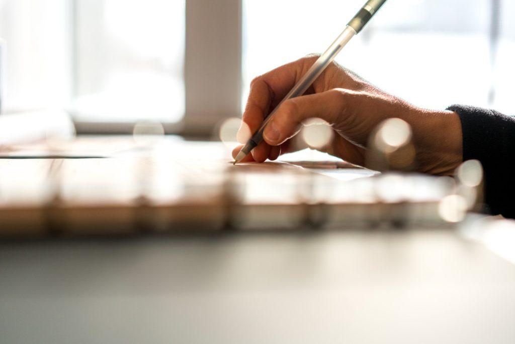 Ausência de pagamento do fgts completo - pessoa escrevendo emk um caderno com uma caneta